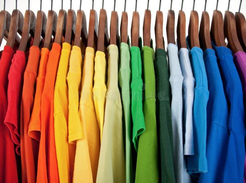 Farben des Regenbogens, Kleidung auf hölzernen Aufhängungen lizenzfreie stockfotos
