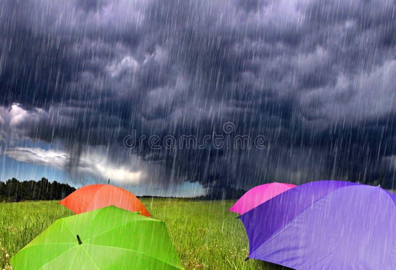 Farben-Regenschirme in den regnerischen Sturm-Wolken stockbilder