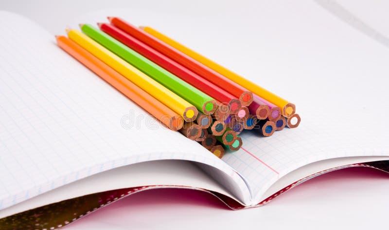 Farbenbleistifte auf Notizbuch stockfotos