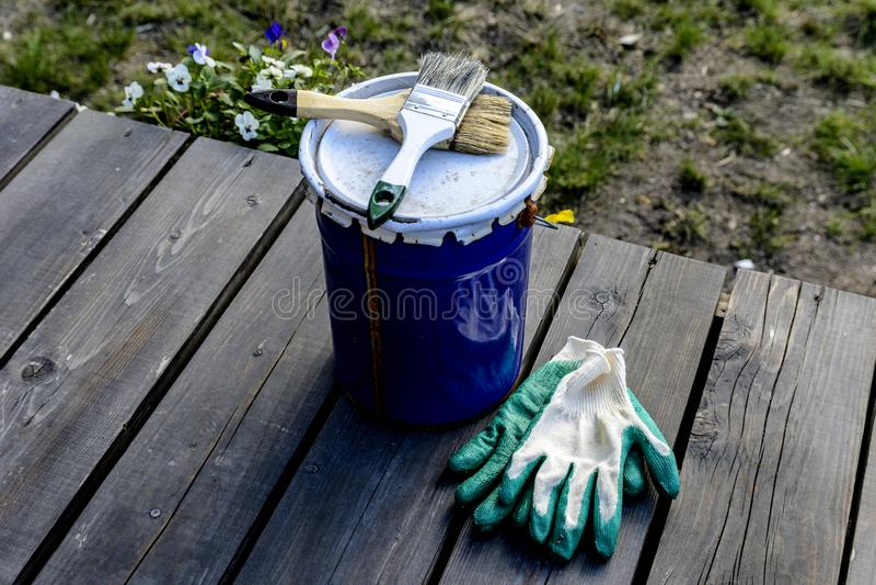 Farbendose, die auf der Terrasse eines Privathauses mit einer B?rste und Handschuhen, bereit ge?ffnet zu sein und gemalt zu werde stockbilder