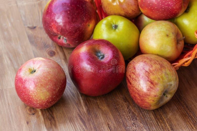 farbenfrohe Äpfel, die aus einem roten Korb mit Korbweide auf eine braune Holzdecke gerollt sind, seitlicher Blick von oben stockbild