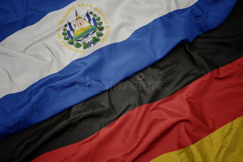 farbenfrohe Flagge von Deutschland und Nationalflagge von el salvador lizenzfreie stockfotos