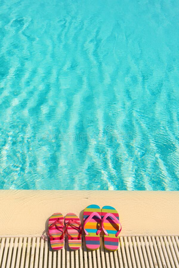 Farbenfrohe Flip Flops am Pool stockfoto