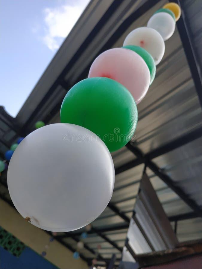 Farbenfrohe Kunststoffkugel hängt Hintergrund blaue Wolke lizenzfreie stockbilder