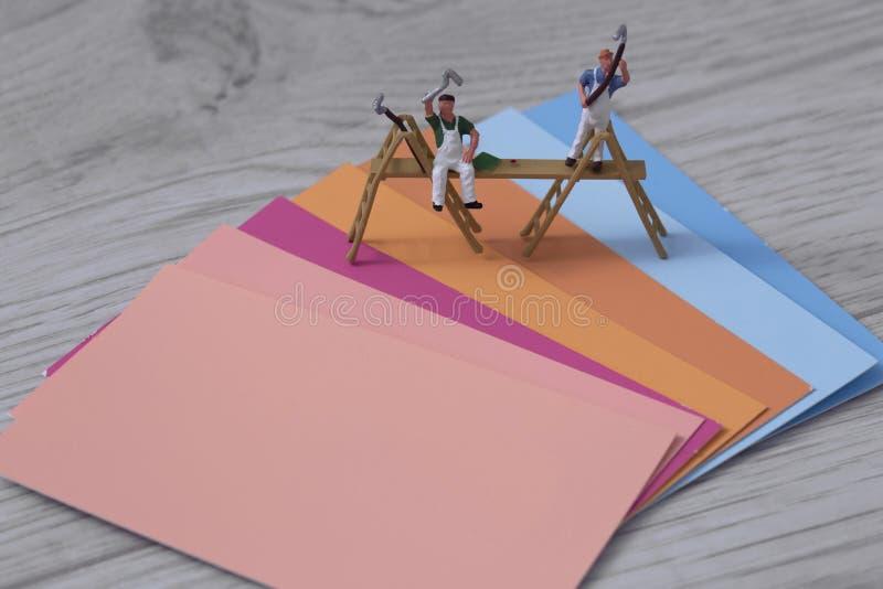 Farbfarben-Musterkarten mit Miniaturmodellbaumalern und -dekorateuren auf einem grauen hölzernen Hintergrund lizenzfreies stockfoto