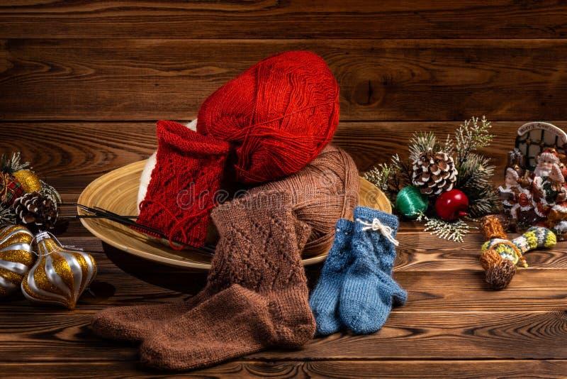 Farbige Bälle des Fadens, der mehrfarbigen gestrickten Socken und des Weihnachtsbaums Dekorationen auf hölzernem Hintergrund stockfotografie