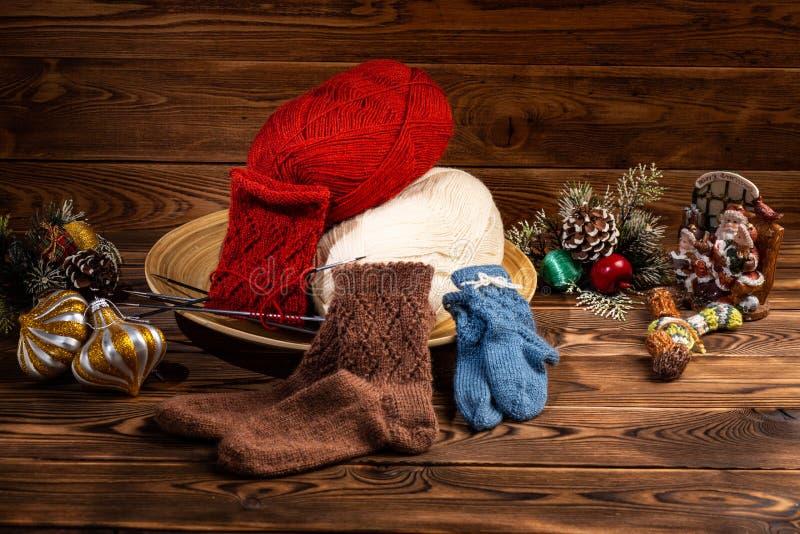 Farbige B?lle des Fadens, der mehrfarbigen gestrickten Socken und des Weihnachtsbaums Dekorationen auf h?lzernem Hintergrund stockfotografie