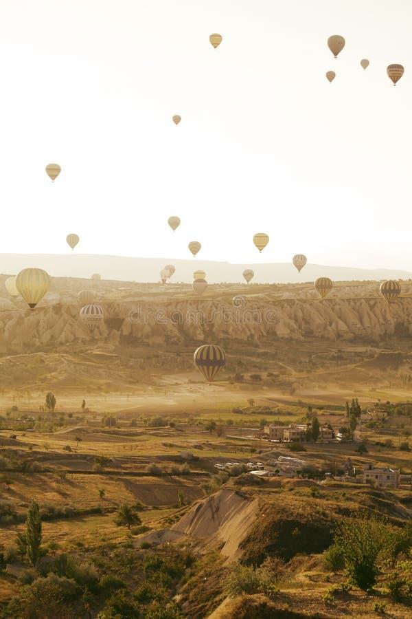 Farbige Ballone im Himmel über einzigartigen szenischen Felsen von Cappadocia stockfoto
