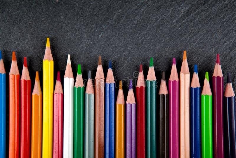 Farbige Bleistifte auf einem schwarzen Steinschiefer stockbild