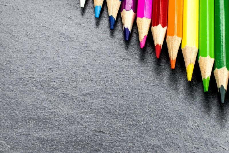 Farbige Bleistifte auf Schiefer lizenzfreie stockbilder