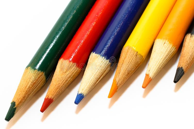 Farbige Bleistifte in den Farben grünen, Rot, Blau, das Gelb, orange und schwarz, ausgerichtet nebeneinander in einem lokalisiert lizenzfreies stockbild