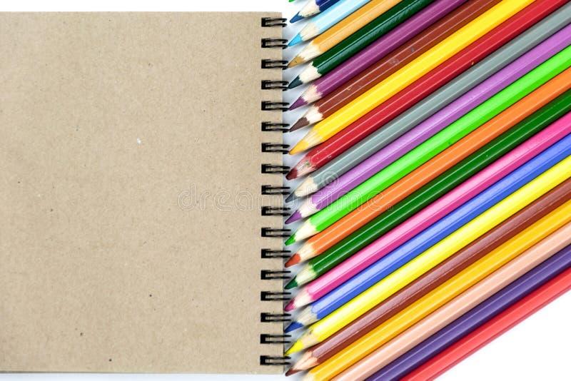 Farbige Bleistifte, Notizbücher auf braunem und beige Hintergrund Brandingbriefpapier-Modellszene, leere Gegenst?nde f?r die Plat lizenzfreie stockbilder
