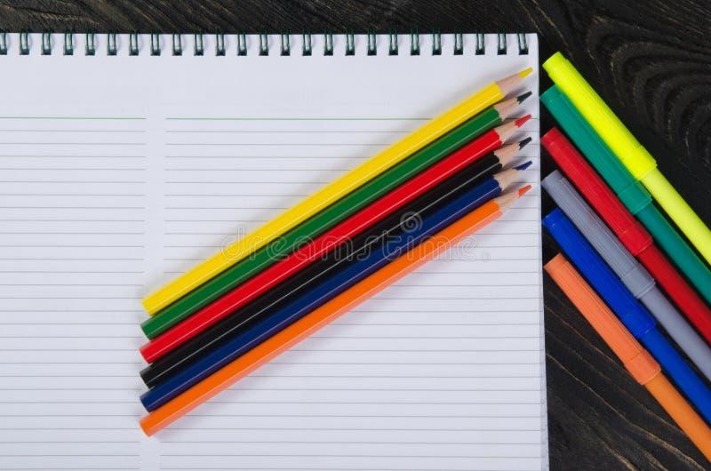 Farbige Bleistifte und ein Notizbuch stockfoto