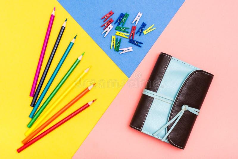 Farbige Bleistifte, farbige Wäscheklammern und Organisator auf einem dreifarbigen Hintergrund lizenzfreie stockfotografie