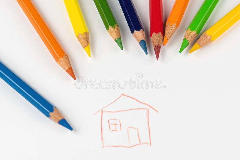 Farbige Bleistifte werden auf ein weißes Blatt Papier zerstreut, auf dem das Haus gemalt wird stockfotografie