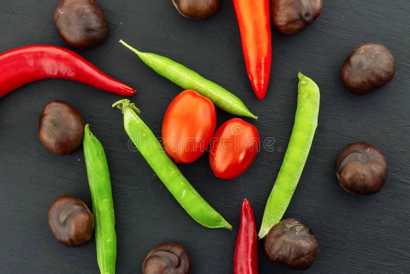 Farbige Gemüseernte Herbsttomaten Kirschtorte grüne Erbsen Braunfrüchte Kastanienpuppe Paprika stockfotos