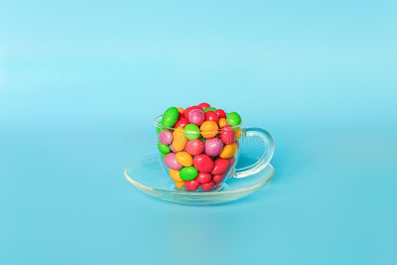 Farbige glasig-glänzende Süßigkeitsbohnen Glasbecher auf der Untertasse gefüllt mit bunten Knopf-förmigen Schokoladen auf blauem  lizenzfreies stockbild
