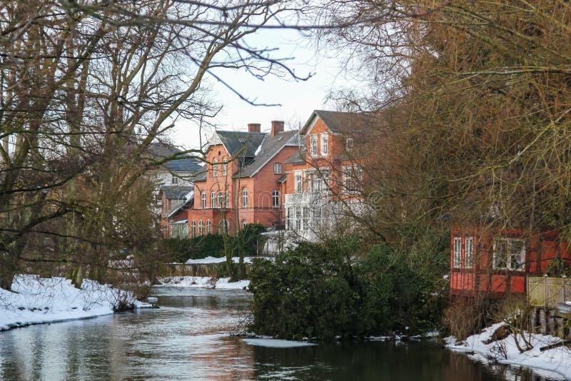 Farbige Häuser und Bäume, die auf den Banken von einem Fluss in Odense, Dänemark stehen lizenzfreie stockfotos