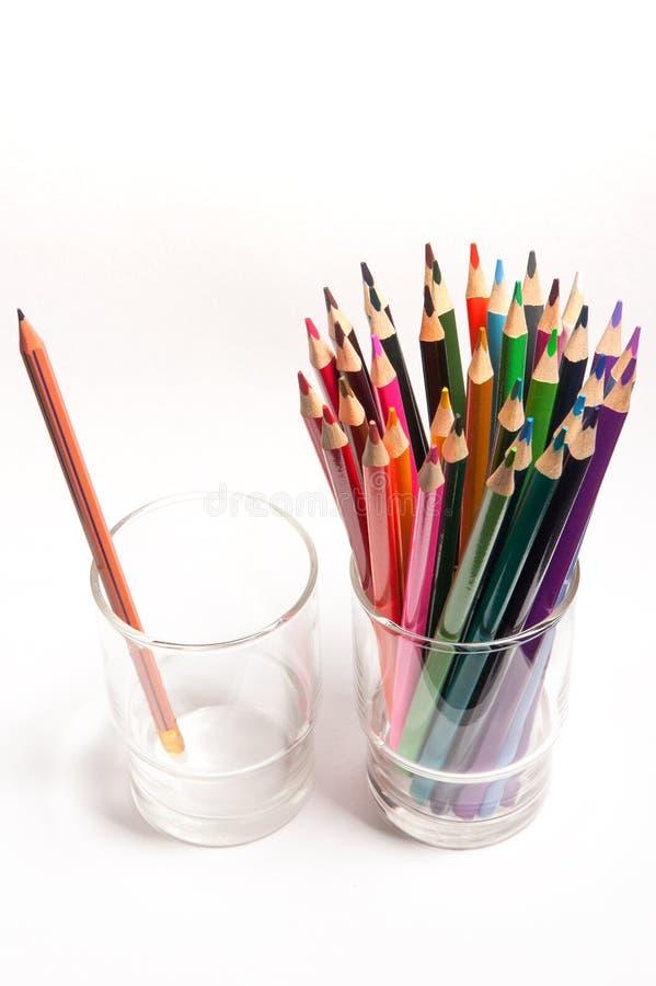 Farbige hölzerne Bleistifte vor einfachem Graphit zeichnen auf Tabelle in den lokalisierten Gläsern an stockfoto