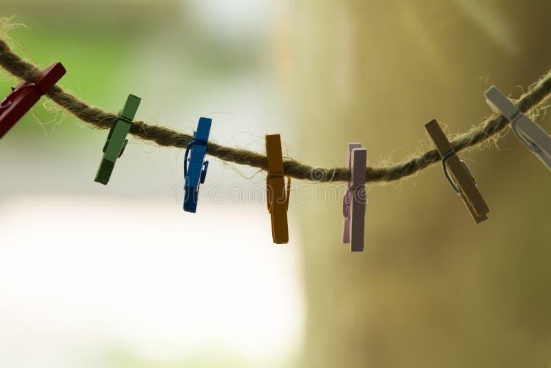 Farbige hölzerne Wäscheklammern, die an einem Draht hängen stockfoto