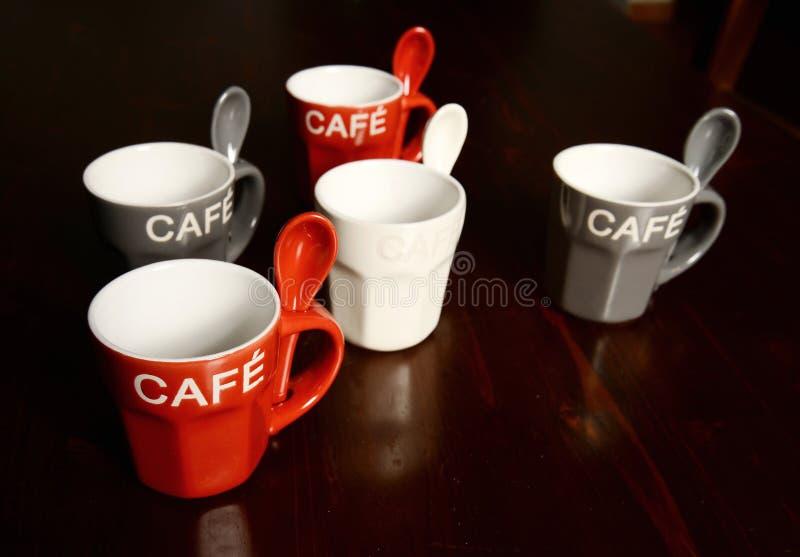 Farbige Kaffeetassen auf Holztisch stockfotografie