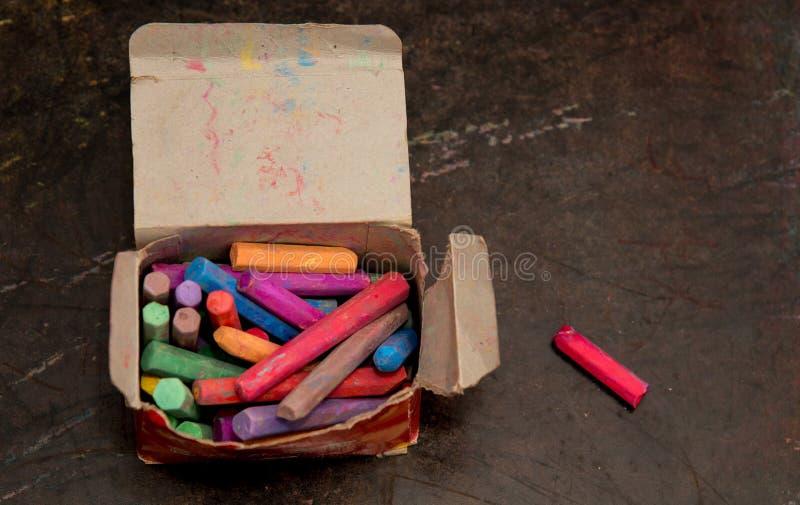 Farbige Kreiden auf Kasten mit Tafel stockbilder