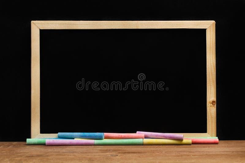 Farbige Kreiden und eine Tafel stockfoto