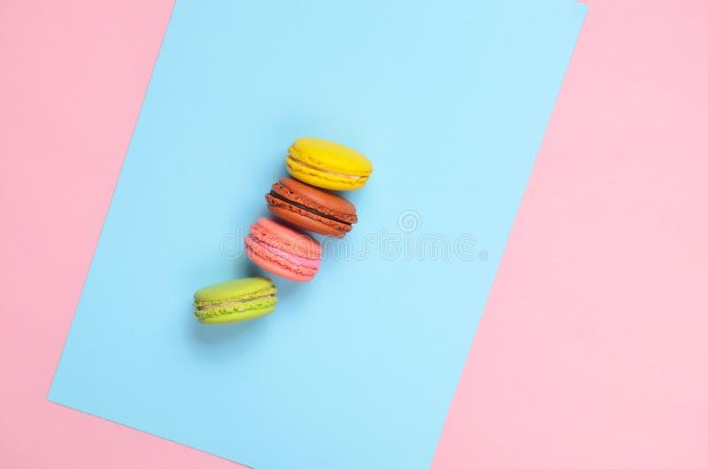 Farbige Makronenplätzchen auf einem blauen rosa Pastellhintergrund Beschneidungspfad eingeschlossen minimalismus stockbild