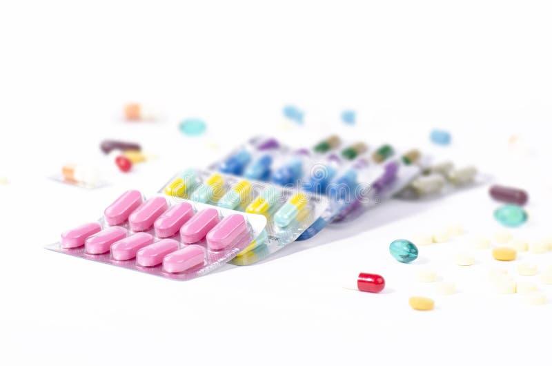 Farbige Medizin in einigen Blisterpackungen mit zerstreuten Pillen stockbilder