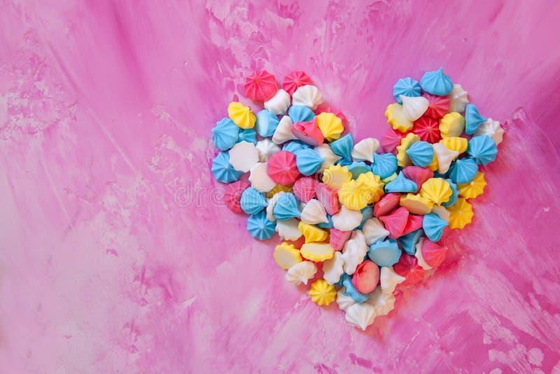 Farbige merengues Pastellkuchen in der Herzform auf rosa Hintergrund von oben lizenzfreie stockfotografie
