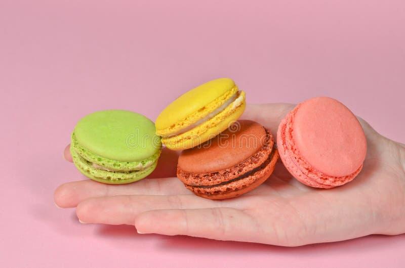 Farbige Nahaufnahme der Makronen in der Hand auf einem rosa Hintergrund stockbild