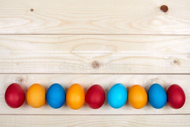 Farbige Osterei-Dekorationslinie über der hellen Holzoberfläche als copyspace festlichen Hintergrundzusammensetzung stockfotos