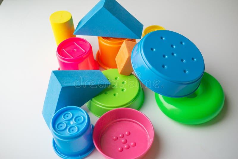 farbige pädagogische Spielwaren für Babys, Würfel, Pyramiden, Kegel, Ringe stockfotos