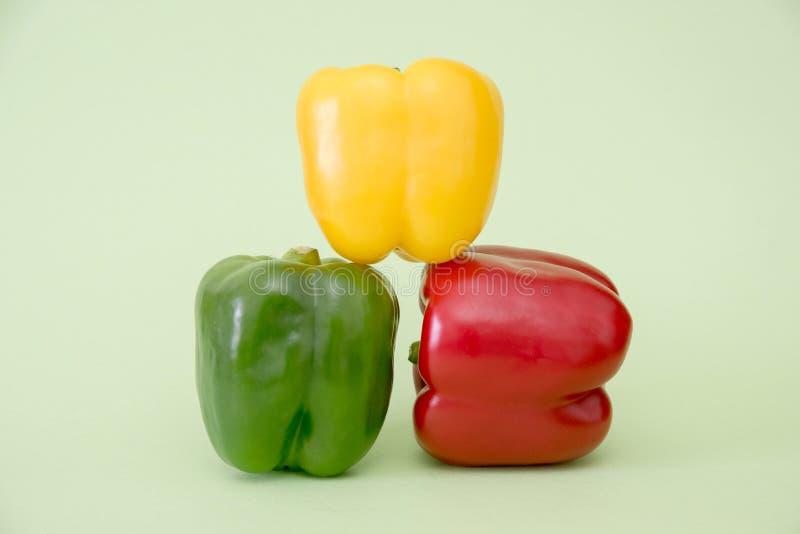 Farbige Paprika auf grünem Hintergrund stockbilder