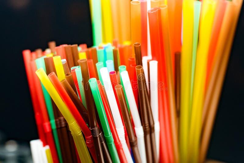 Farbige Plastikcocktailrohre, die in einer Glasplatteansicht, Trinkhalme stehen lizenzfreies stockfoto