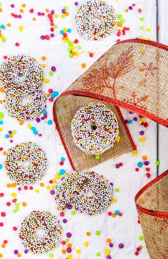 Farbige Schokoladenringe mit Weihnachtsdekoration lizenzfreie stockbilder