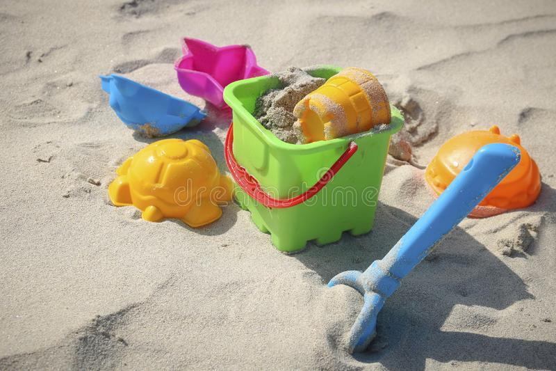 Farbige Spielwaren auf dem sandigen Strand stockbild