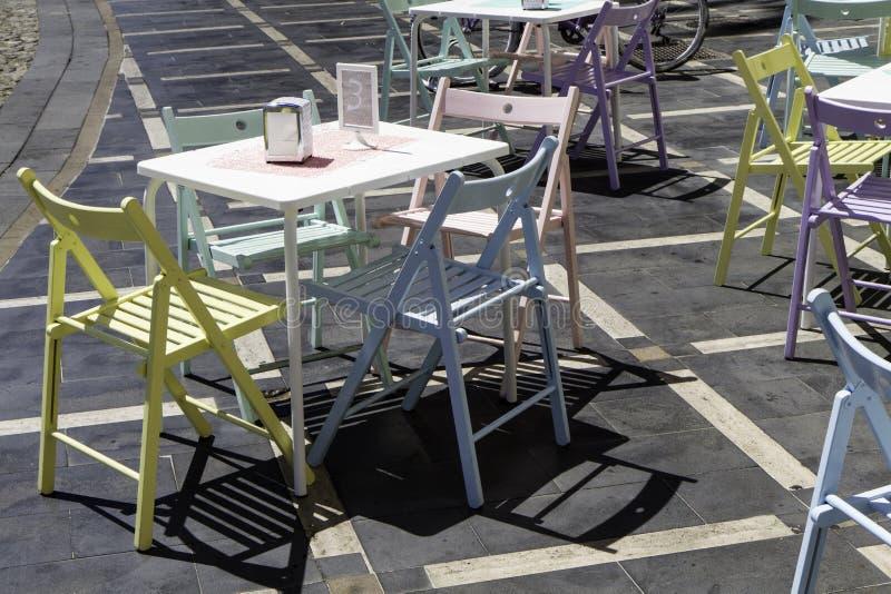 Farbige Tabellen und Stühle der Weinlese durch ein Café lizenzfreie stockfotos