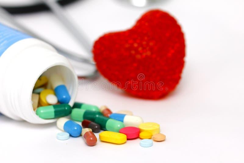 Farbige Tabletten mit rotem Herzen lizenzfreie stockfotografie