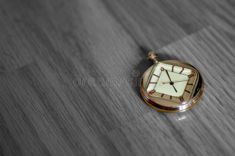 Farbige Taschenuhr, die auf einem hölzernen strukturierten Boden in Schwarzweiss liegt stockbild