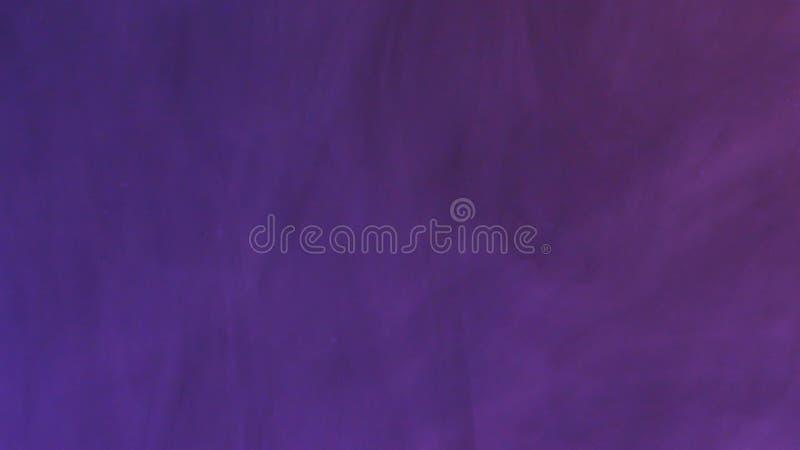 Farbige Tintenwolke wächst im Wasser auf purpurrotem Hintergrund stockfotografie