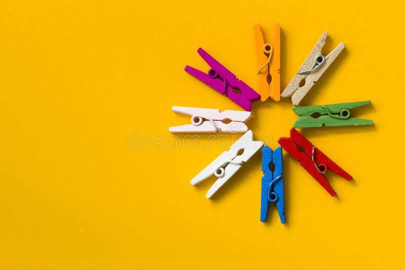 Farbige Wäscheklammern auf einem gelben Hintergrund stockbild