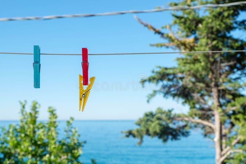 Farbige Wäscheklammern, die an einem weißen Kabel mit blauem See- und Himmelhintergrund hängen lizenzfreie stockfotos