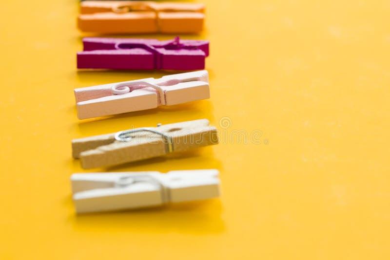 Farbige W?scheklammern auf einem gelben Hintergrund lizenzfreie stockfotografie