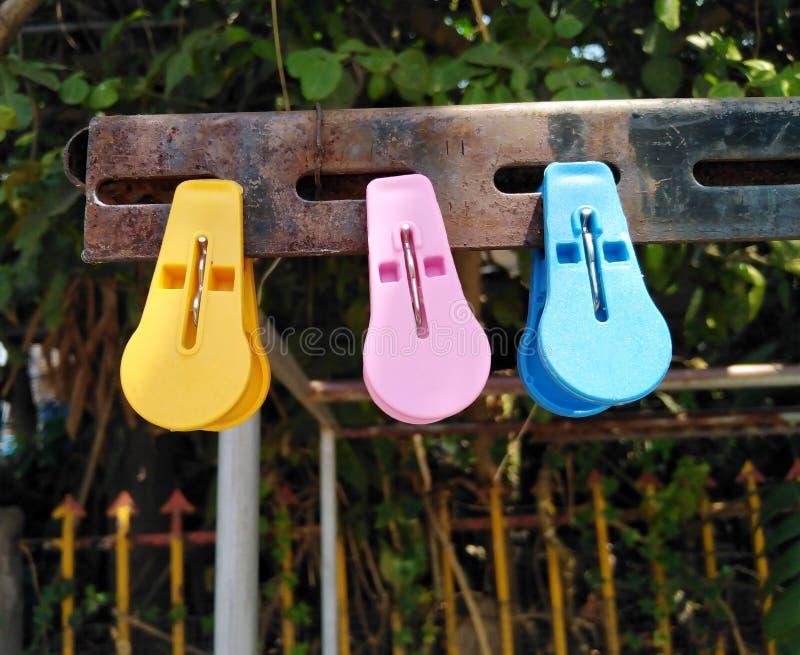 Farbiger Plastik mit drei Wäscheklammern brihht auf Stahl mit Rost lizenzfreie stockbilder