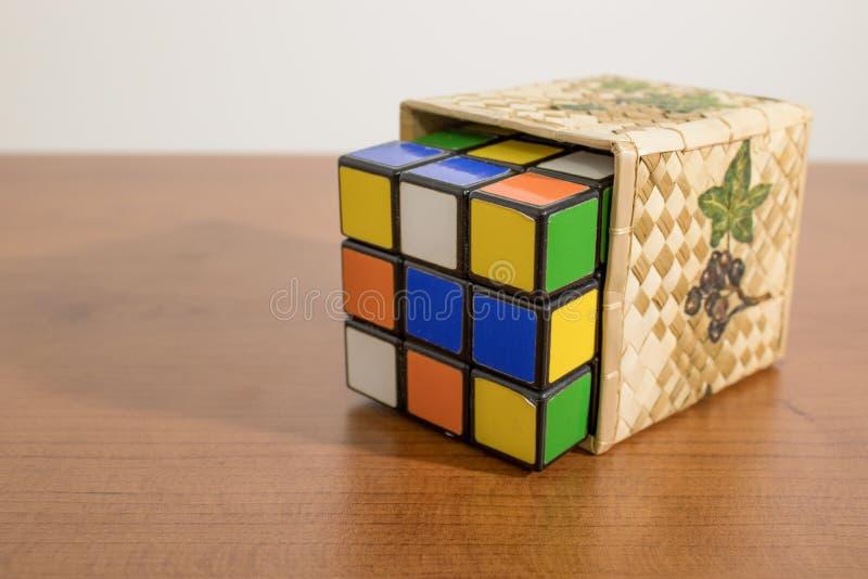 Farbiger rubik Würfel in einem Kasten auf einer Tabelle lizenzfreies stockfoto