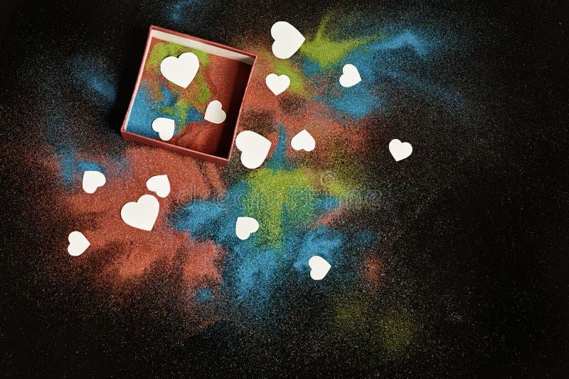 Farbiger Sand und weiße Herzen stockfotos