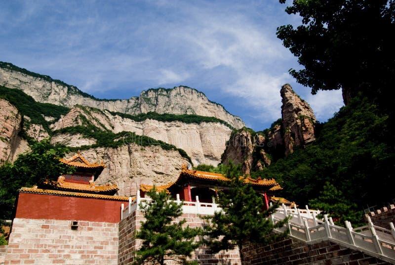 Farbiger Tempel und roter Berg stockfoto