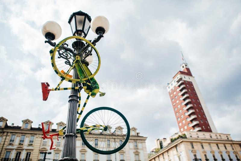 Farbiges Fahrrad wird nahe einem Laternenpfahl, eine Metapher, ein Kunstgegenstand, eine Nebenkultur Italien, Turin geparkt, lizenzfreie stockfotografie