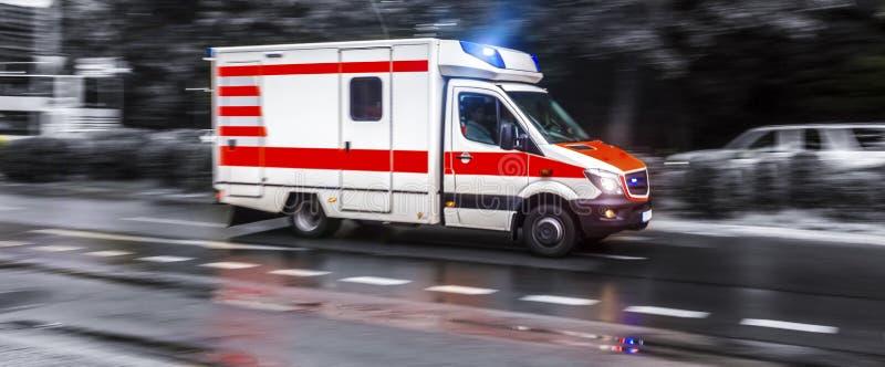 Farbiges Krankenwagenauto, das in Schwarzweiss beschleunigt stockfotografie